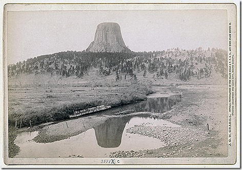 Title: Devil's TowerDistant view of Devils Tower and reflection of tower in stream in foreground. 1890.Repository: Library of Congress Prints and Photographs Division Washington, D.C. 20540